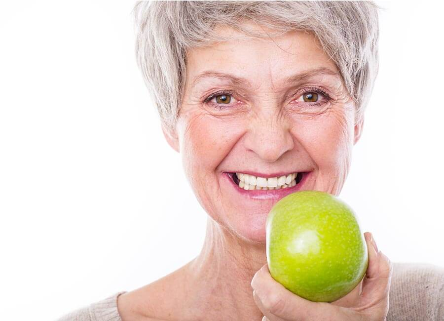 Elderly Women Eating Apple