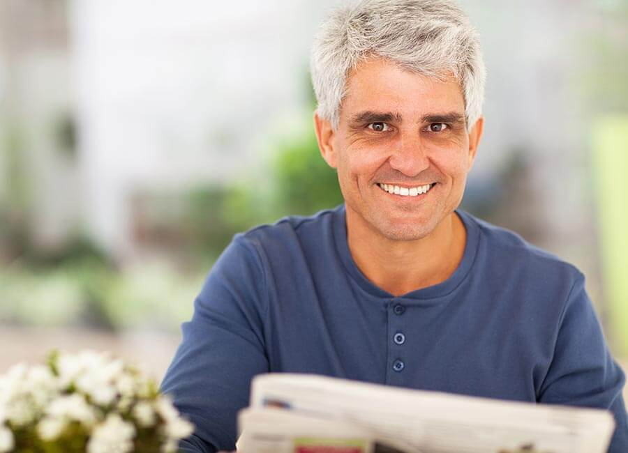 Gentleman Smiling Whilst Reading Newspaper