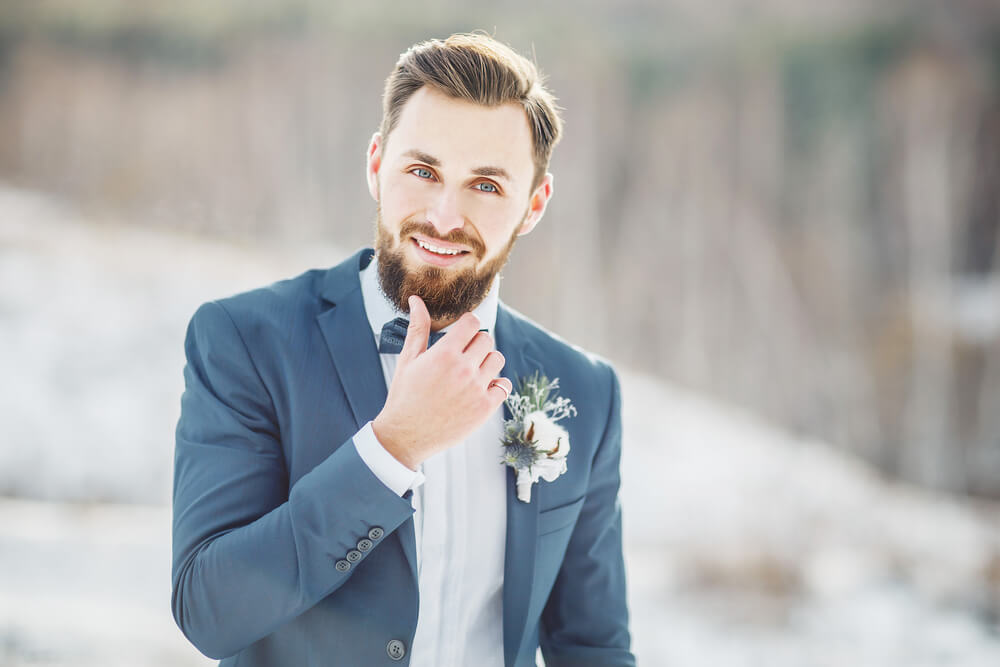 Groom Touching Beard Whilst Smiling